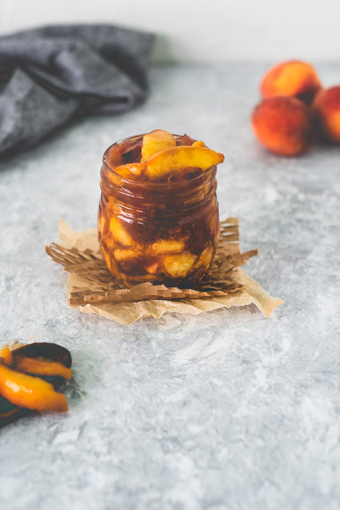 A jar of Fresh Peach Pie Filling sitting on top of a square of parchment and meshed paper with a spoonful sitting in front and a bunch of peaches behind.