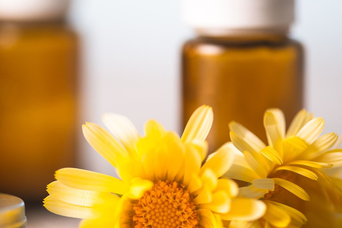 Essential Oil Bottles sitting behind fresh yellow calendula flowers
